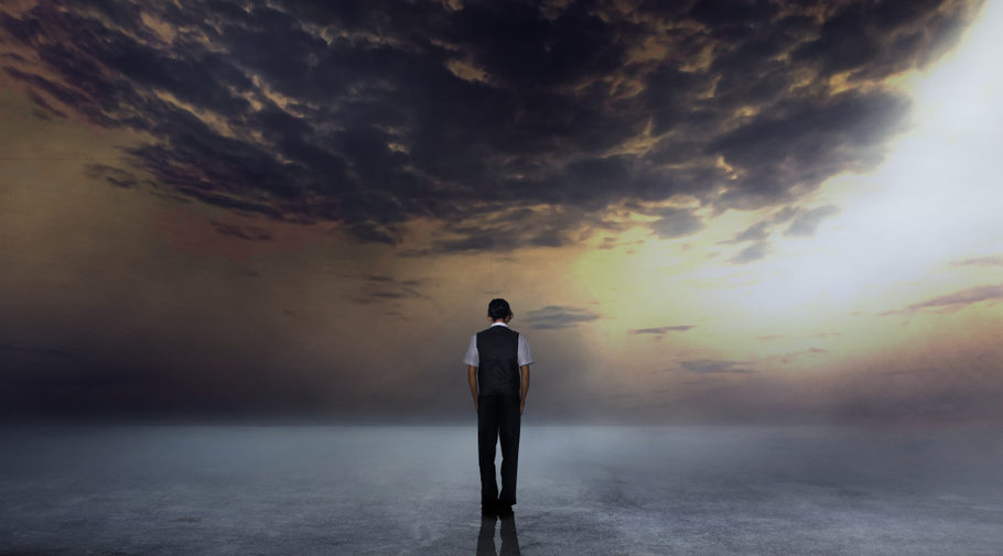 elegant businessman standing on dark concentrate with twilight sky.